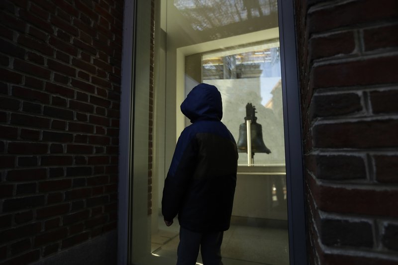 A young boy visiting Independence National Historical Park peers through a window of the closed building housing the Liberty Bell, Wednesday, Dec. (AP Photo/Matt Slocum)