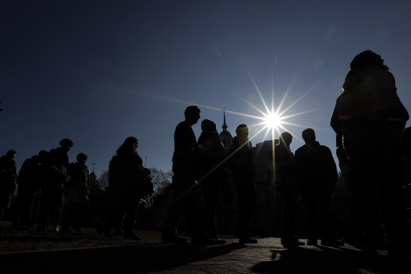 Tourists to Independence National Historical Park line up to peer through a window of the closed building housing the Liberty Bell, Wednesday, Dec. (AP Photo/Matt Slocum)