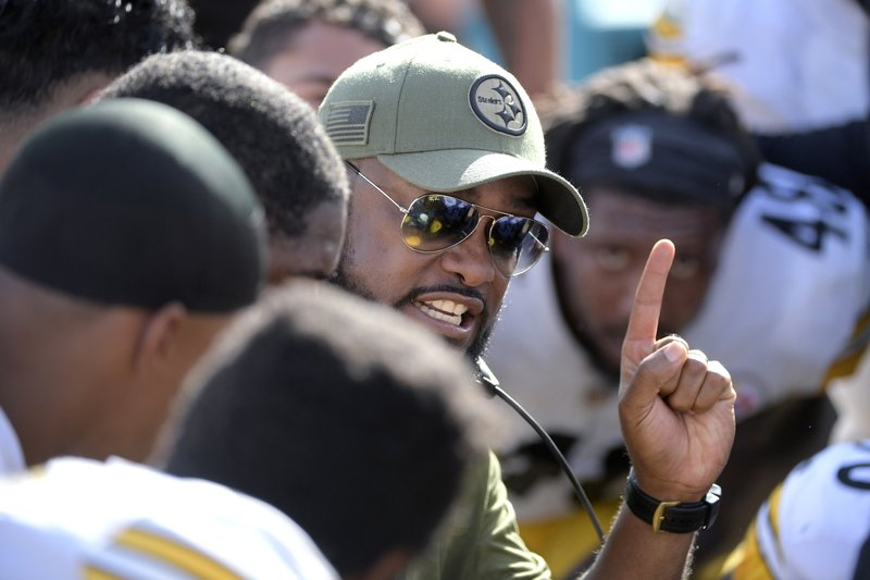 File-This Nov. 18, 2018, file photo shows Pittsburgh Steelers head coach Mike Tomlin, center, talking to his players on the bench during the first half of an NFL football game against the Jacksonville Jaguars in Jacksonville, Fla. (AP Photo/Phelan M. Ebenhack, File)