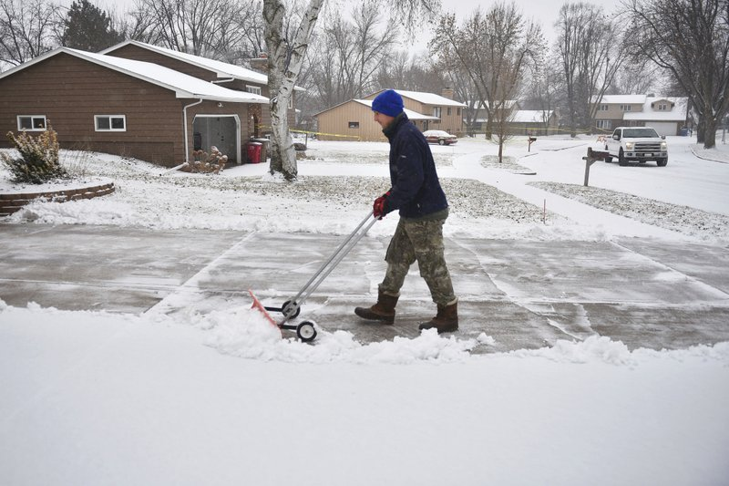 In this Wednesday, Dec. 26, 2018 photo, Lance Nieuwenhuis shovels snow out of his driveway in Sioux Falls, S. (Briana Sanchez/The Argus Leader via AP)
