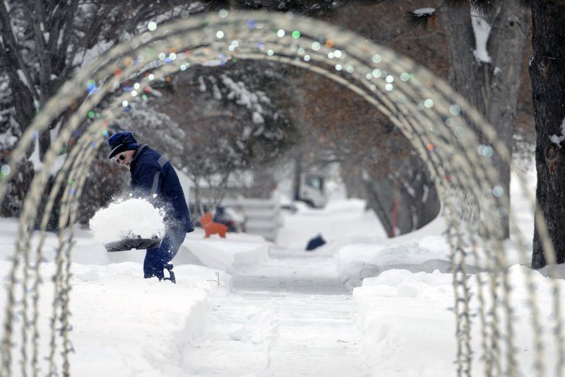 A Christmas outdoor decoration placed over a sidewalk frames Bjorn Gronbeck as he removes snow from a driveway on 17th Street Thursday, Dec. (Mike McCleary/The Bismarck Tribune via AP)