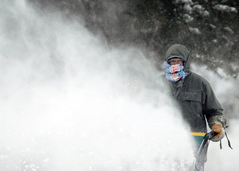 Errol Behm uses a scarf to shield his face from the blow-back of snow caused by the gusty winds as he clears a sidewalk with a snow blower near Fourth Street Thursday, Dec. (Mike McCleary/The Bismarck Tribune via AP)