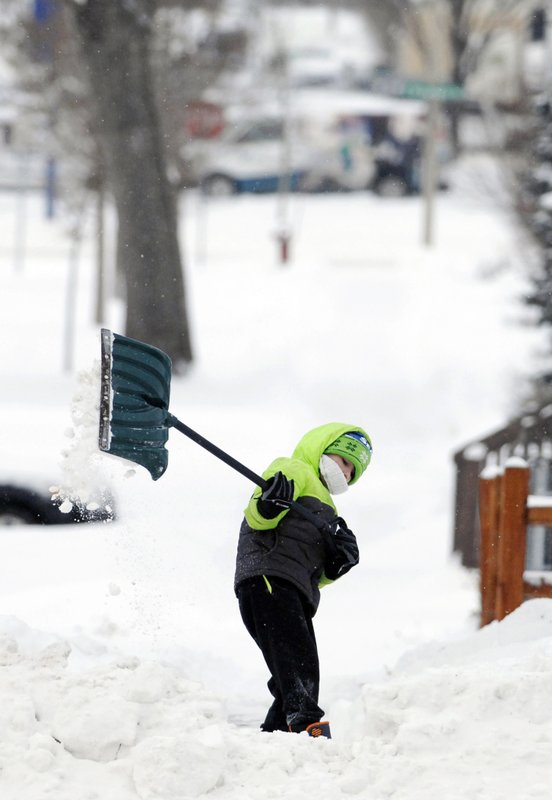 Vincent Schaff, 8, uses all of his body as he heaves a shovel full of snow from the sidewalk of his grandmother's home along Rosser Avenue Thursday, Dec. (Mike McCleary/The Bismarck Tribune via AP)
