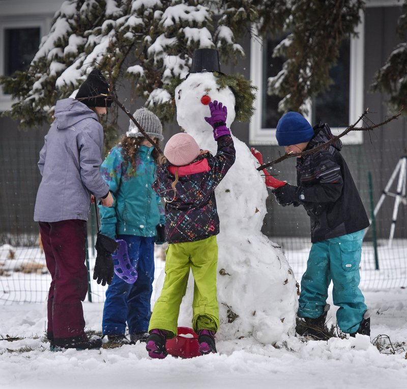 A bright red nose adds a festive touch to a snowman under construction by children after a fresh snowfall Thursday, Dec. (Dave Schwarz/The St. Cloud Times via AP)