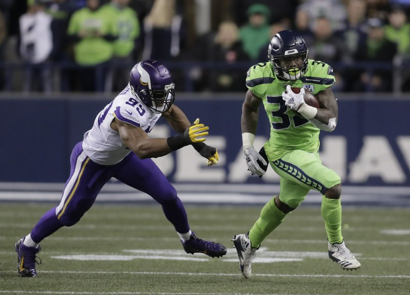 File-This Dec. 10, 2018, file photo shows Seahawks' Chris Carson carrying the ball as Minnesota Vikings' Danielle Hunter gives chase in the first half of an NFL football game, in Seattle. Seattle (9-6) already has its playoff spot wrapped up, although a win would get Seattle to 10 wins for the sixth time in Carroll's tenure and ensure the Seahawks are the No. 5 seed in the NFC, setting up a wild-card round matchup at Dallas on the opening weekend of the postseason.   (AP Photo/Stephen Brashear, File)