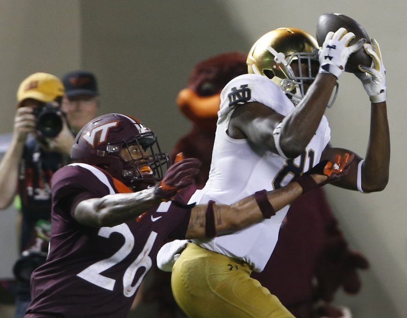 File-This Oct. 6, 2018, file photo shows Notre Dame wide receiver Miles Boykin (81) making a catch over Virginia Tech defensive back Jovonn Quillen (26) during the second half of an NCAA college football game in Blacksburg, Va. (AP Photo/Steve Helber, File)