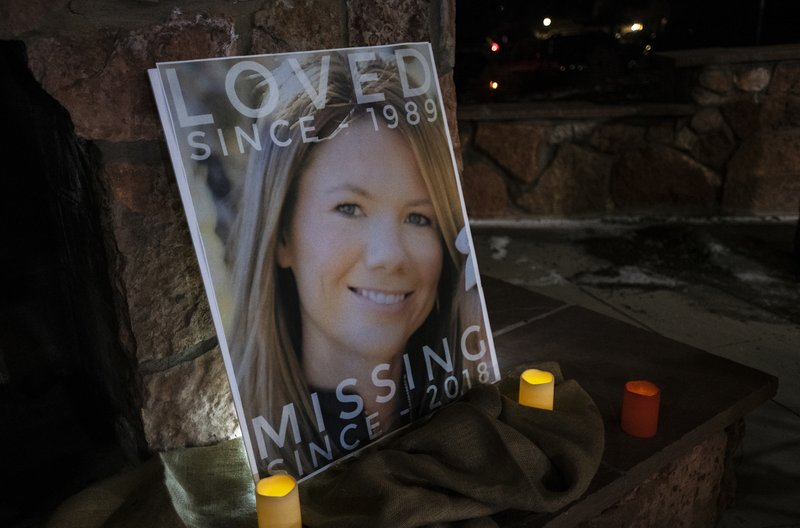 A poster with the picture of the missing Kelsey Berreth is propped up with candles for a vigil Memorial Park in Woodland Park, Colo. (Kelsey Brunner/The Gazette via AP)