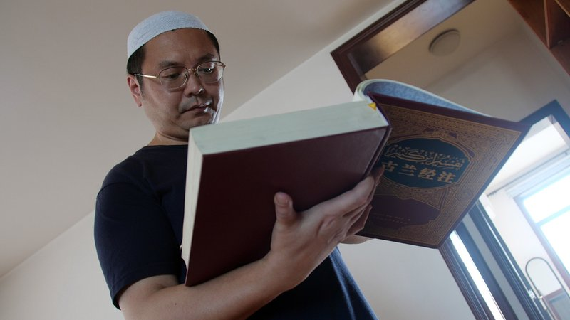 In this Sept. 28, 2018, photo, Muslim Chinese poet Cui Haoxin reads an Arabic prayer from a Quran in his home in the city of Jinan in China's eastern province of Shandong. (AP Photo/Sam McNeil)