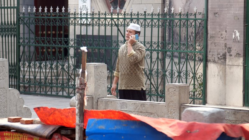 In this Sept. 27, 2018, photo, a Hui Muslim man talks on his mobile phone outside the Nandashi Great Southern Mosque in Jinan in China's eastern province of Shandong, where an ancient Muslim minority known as the Hui have lived for centuries. (AP Photo/Sam McNeil)