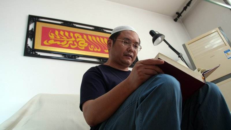 In this Sept. 28, 2018 photo, Muslim Chinese poet Cui Haoxin reads an Arabic prayer from a Quran in his home underneath a tapestry woven by his mother reading in Arabic
