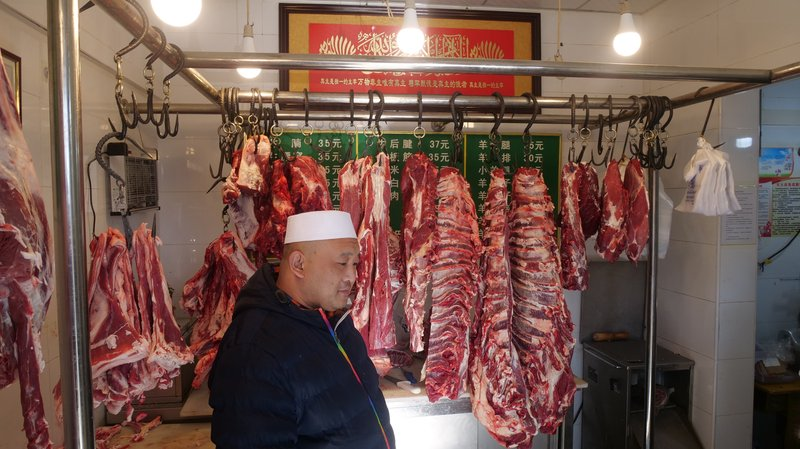 In this Dec. 7, 2018, photo, Ma Changli, 39, stands in the butcher shop that he has run in the Islamic neighborhood of Niujie for 5 years after moving from Hubei to Beijing 20 years ago. (AP Photo/Sam McNeil)