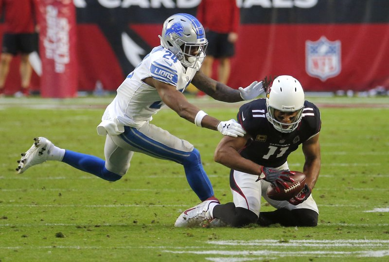 FILE - In this Dec. 9, 2018, file photo, Arizona Cardinals wide receiver Larry Fitzgerald (11) makes his 1,282nd career catch during the second half of an NFL football game as Detroit Lions cornerback Nevin Lawson (24) defends in Glendale, Ariz. (AP Photo/Rick Scuteri, File)