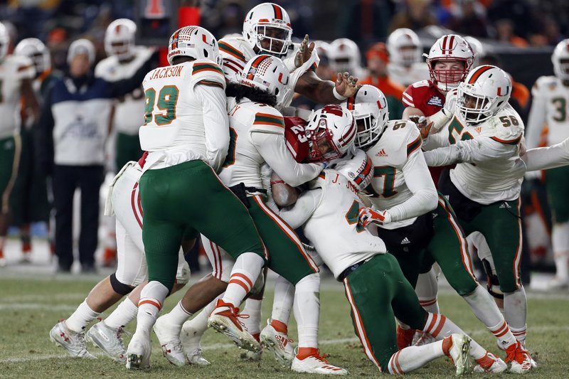 Wisconsin running back Jonathan Taylor (23) is tackled by several Miami players during the first half of the Pinstripe Bowl NCAA college football game Thursday, Dec. (AP Photo/Adam Hunger)