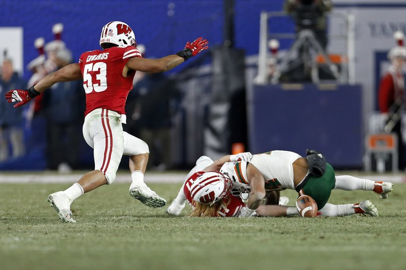 Miami running back Travis Homer fumbles the ball while being tackled by Wisconsin linebacker Andrew Van Ginkel during the first half of the Pinstripe Bowl NCAA college football game Thursday, Dec. (AP Photo/Adam Hunger)