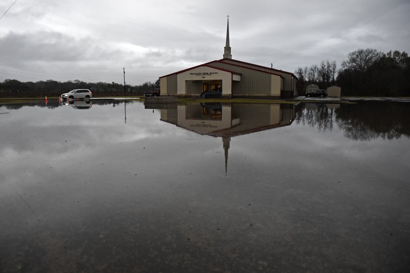 High water encroaches on the Treasures From Heaven Ministry on Mickens Road, Thursday, Dec. 27, 2018, as severe weather impacts the area in Baton Rouge, La. (Hilary Scheinuk/The Advocate via AP)