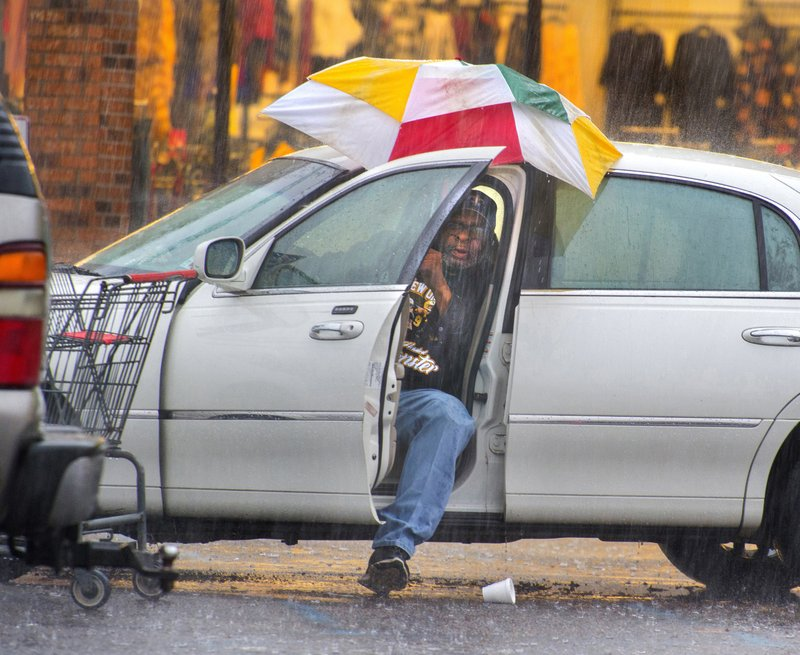 Harry Anderson tries to stay relatively dry as he maneuvers his umbrella into position before slipping out of his car during a steady rainstorm, Thursday, Dec 27, 2018, in Baton Rouge, La. (Travis Spradling/The Advocate via AP)