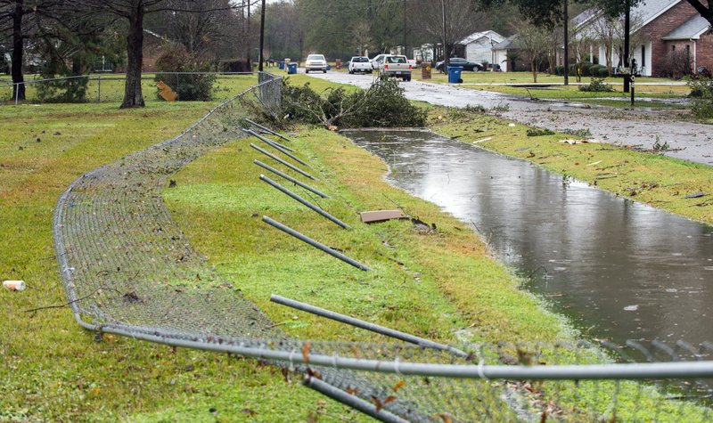 Wind damage to a fence, possibly caused by a small tornado, is pictured on La Butte Street following heavy rain and thunderstorms on Thursday, Dec. (Leslie Westbrook/The Advocate via AP)