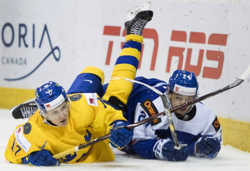 Sweden's Filip Sveningsson (17) fights for control of the puck with Slovakia's Jozef Balaz (24) during the first period of a world junior hockey championship game Thursday, Dec. (Jonathan Hayward/The Canadian Press via AP)