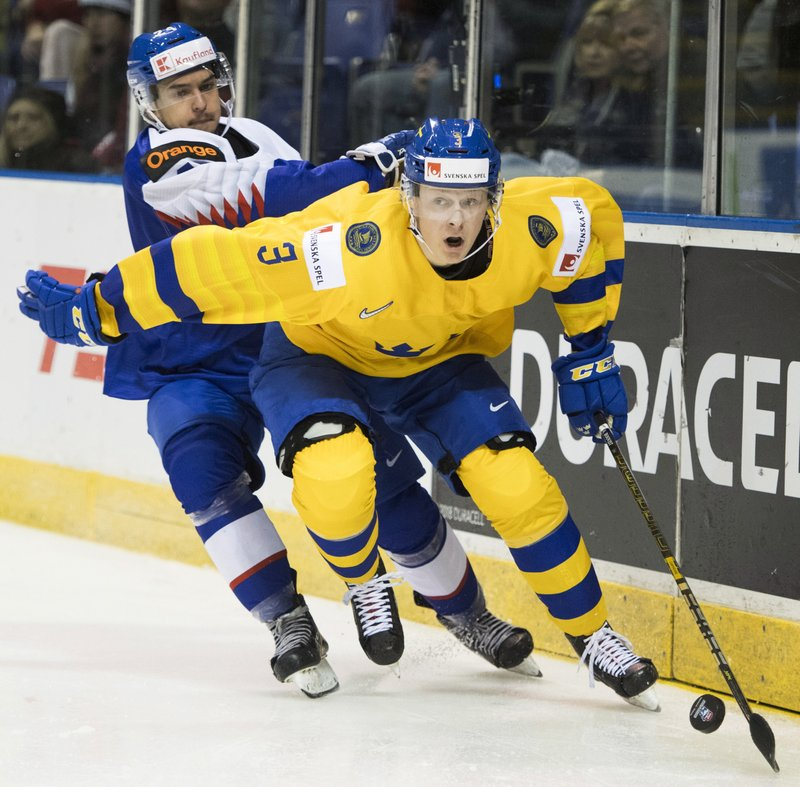 Sweden's Adam Boqvist (3) fights for control of the puck with Slovakia's Jozef Balaz (24) during the second period of a world junior hockey championship game Thursday, Dec. (Jonathan Hayward/The Canadian Press via AP)