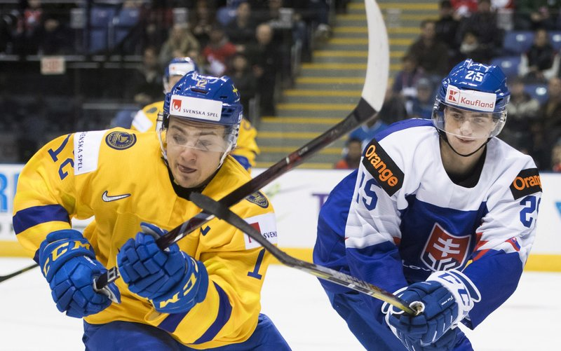 Sweden's Erik Brannstrom (12) fights for control of the puck with Slovakia's Martin Pospisil (25) during the second period of a world junior hockey championship game Thursday, Dec. (Jonathan Hayward/The Canadian Press via AP)