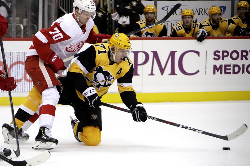 Pittsburgh Penguins' Evgeni Malkin (71) gets off a pass as he falls to the ice with Detroit Red Wings' Christoffer Ehn (70) defending during the second period of an NHL hockey game in Pittsburgh, Thursday, Dec. (AP Photo/Gene J. Puskar)