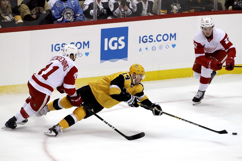 Pittsburgh Penguins' Tanner Pearson (14) gets off a pass as he falls to the ice with Detroit Red Wings' Luke Glendening (41) defending during the first period of an NHL hockey game in Pittsburgh, Thursday, Dec. (AP Photo/Gene J. Puskar)