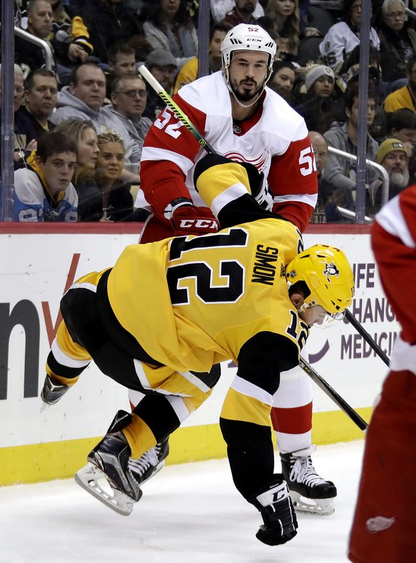 Pittsburgh Penguins' Dominik Simon (12) is hit by Detroit Red Wings' Jonathan Ericsson (52) during the second period of an NHL hockey game in Pittsburgh, Thursday, Dec. (AP Photo/Gene J. Puskar)