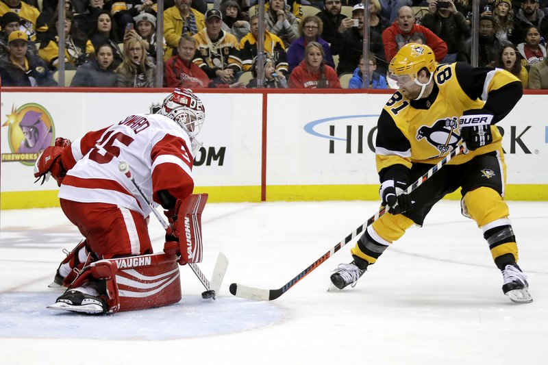 Pittsburgh Penguins' Phil Kessel (81) puts a shot between the pads of Detroit Red Wings goaltender Jimmy Howard (35) for his first of two second-period goals during an NHL hockey game in Pittsburgh, Thursday, Dec. (AP Photo/Gene J. Puskar)
