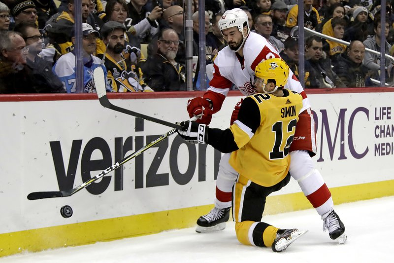 Pittsburgh Penguins' Dominik Simon (12) is checked off the puck by Detroit Red Wings' Jonathan Ericsson (52) during the second period of an NHL hockey game in Pittsburgh, Thursday, Dec. (AP Photo/Gene J. Puskar)