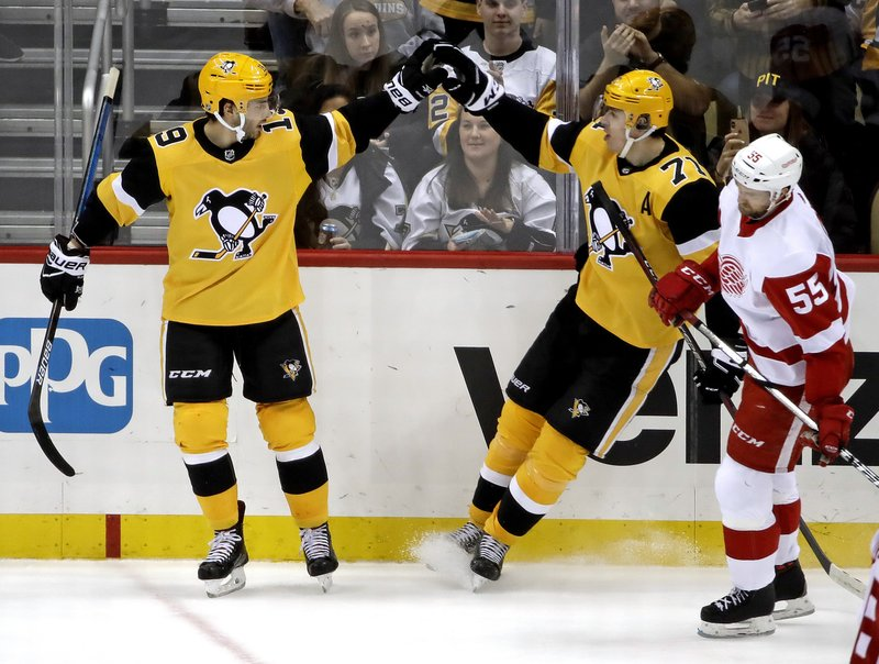 Pittsburgh Penguins' Derick Brassard (19) celebrates his empty-net goal with Evgeni Malkin (71) as Detroit Red Wings' Niklas Kronwall (55) skates back to the bench during the third period of an NHL hockey game in Pittsburgh, Thursday, Dec. (AP Photo/Gene J. Puskar)