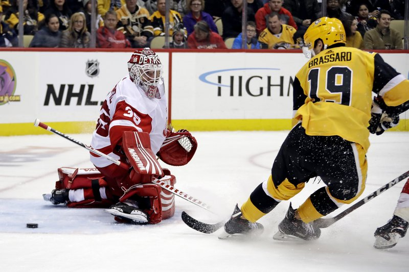 Pittsburgh Penguins' Derick Brassard (19) deflects the puck past Detroit Red Wings goaltender Jimmy Howard (35) for a goal during the second period of an NHL hockey game in Pittsburgh, Thursday, Dec. (AP Photo/Gene J. Puskar)