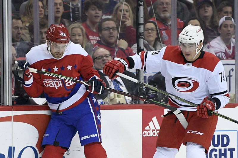 Washington Capitals center Evgeny Kuznetsov (92), of Russia, battles against Carolina Hurricanes left wing Micheal Ferland (79) during the second period of an NHL hockey game, Thursday, Dec. (AP Photo/Nick Wass)