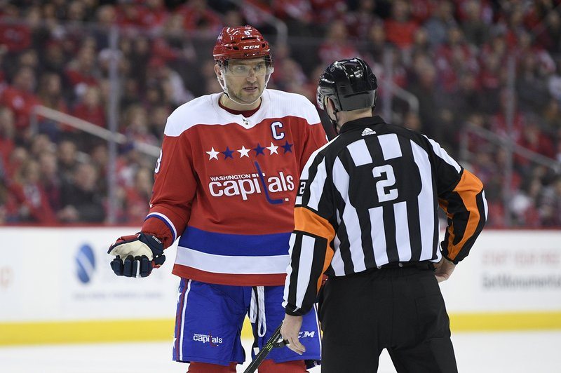 Washington Capitals left wing Alex Ovechkin (8), of Russia, talks with referee Jon McIsaac (2) during the first period of an NHL hockey game against the Carolina Hurricanes, Thursday, Dec. (AP Photo/Nick Wass)