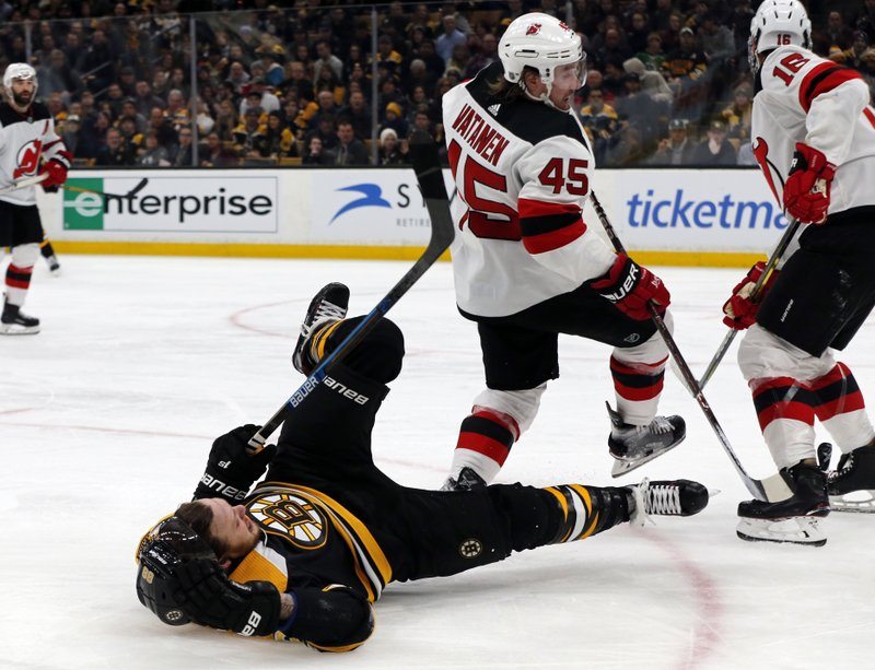 Boston Bruins right wing David Pastrnak (88) is knocked to the ice as he competes with New Jersey Devils defenseman Sami Vatanen (45) for the puck the second period of an NHL hockey game Thursday, Dec. (AP Photo/Elise Amendola)