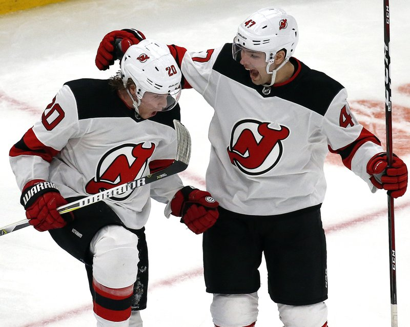 New Jersey Devils center Blake Coleman (20) celebrates his goal with teammate John Quenneville (47) during the third period of an NHL hockey game against the Boston Bruins, Thursday, Dec. (AP Photo/Elise Amendola)