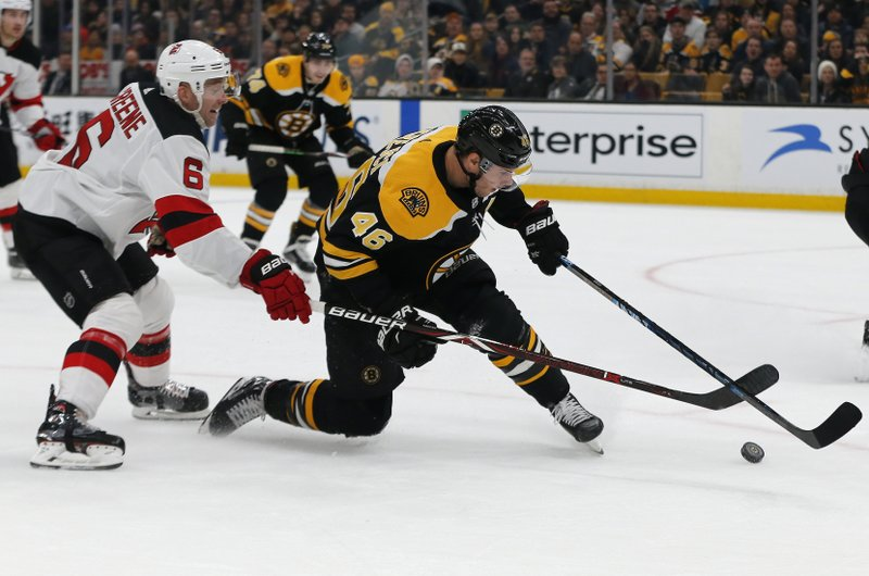 New Jersey Devils defenseman Andy Greene (6) and Boston Bruins center David Krejci (46) reach for the puck during the second period of an NHL hockey game Thursday, Dec. (AP Photo/Elise Amendola)
