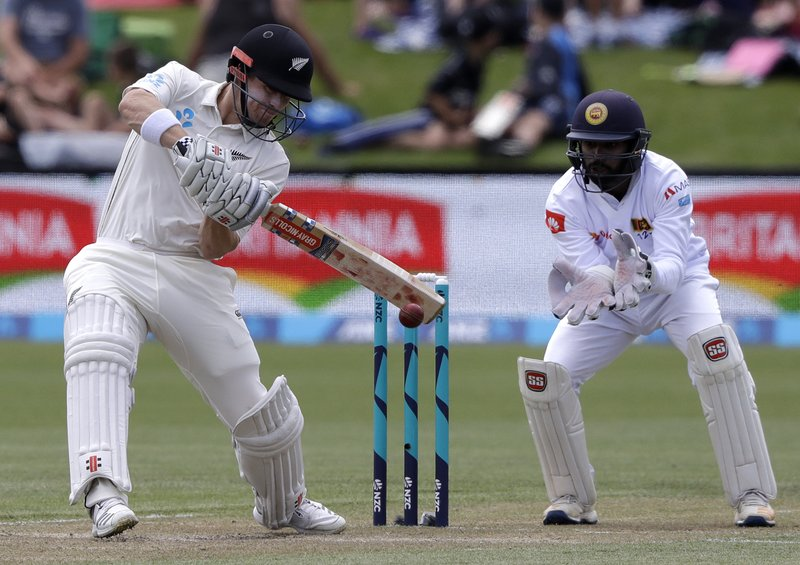 New Zealand's Henry Nicholls plays a cut shot as Sri Lanka's wicketkeeper Niroshan Dickwella watches during play on day three of the second cricket test between New Zealand and Sri Lanka at Hagley Oval in Christchurch, New Zealand, Friday, Dec. (AP Photo/Mark Baker)