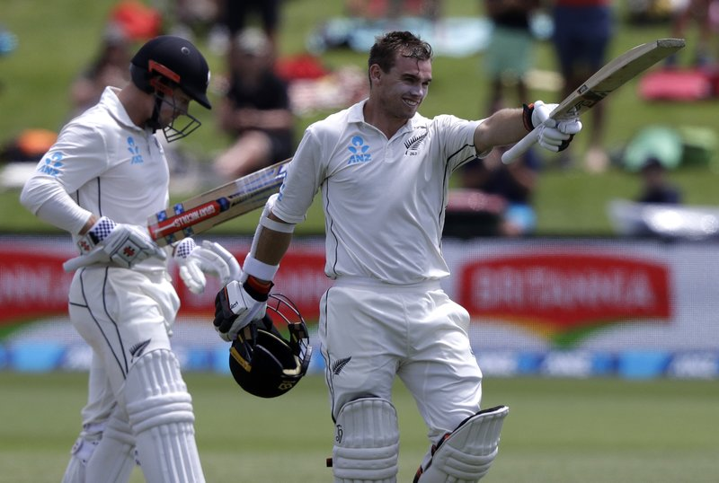New Zealand's Tom Latham celebrates after reaching his century as teammate Henry Nicholls watches during play on day three of the second cricket test between New Zealand and Sri Lanka at Hagley Oval in Christchurch, New Zealand, Friday, Dec. (AP Photo/Mark Baker)