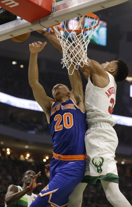 Milwaukee Bucks' Giannis Antetokounmpo, right, blocks the shot by New York Knicks' Kevin Knox during the first half of an NBA basketball game Thursday, Dec. (AP Photo/Jeffrey Phelps)