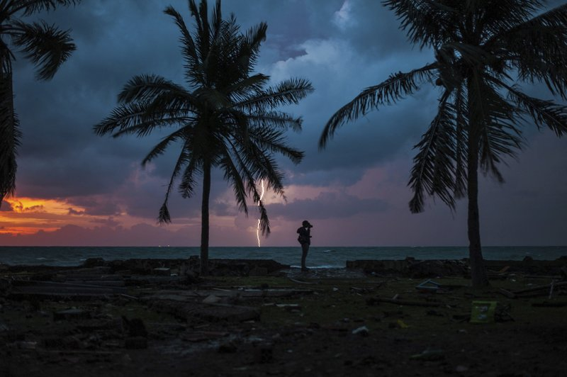 In this Tuesday, Dec. 25, 2018, file photo, a photojournalist is silhouetted by the sunset as a lightning strike at a resort affected by Saturday's tsunami in Carita, Indonesia. (AP Photo/Fauzy Chaniago, File)