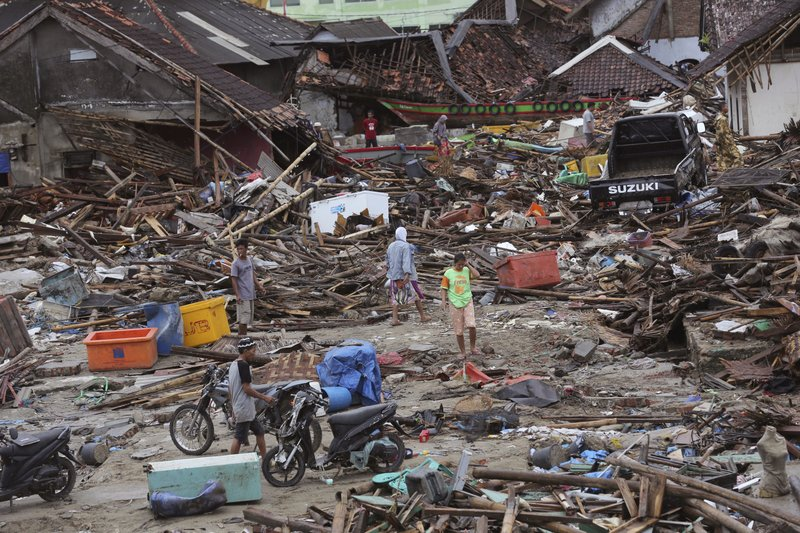 In this Tuesday, Dec. 25, 2018, file photo, people inspect the damage at a tsunami-ravaged village in Sumur, Indonesia. (AP Photo/Tatan Syuflana, File)