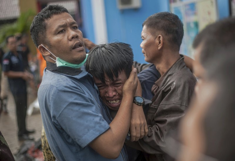 In this Sunday, Dec. 23, 2018, file photo, a man reacts after identifying his relative among the bodies of tsunami victims in Carita, Indonesia. (AP Photo/Fauzy Chaniago, File)