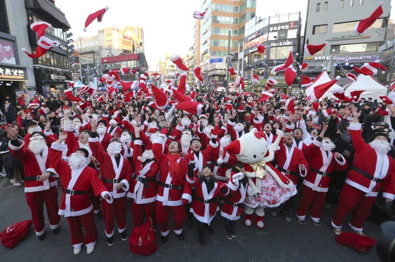 In this Monday, Dec. 24, 2018, file photo, volunteers clad in Santa Claus costumes throw their hats in the air as they gather to deliver gifts for the poor in downtown Seoul, South Korea. (AP Photo/Ahn Young-joon, File)