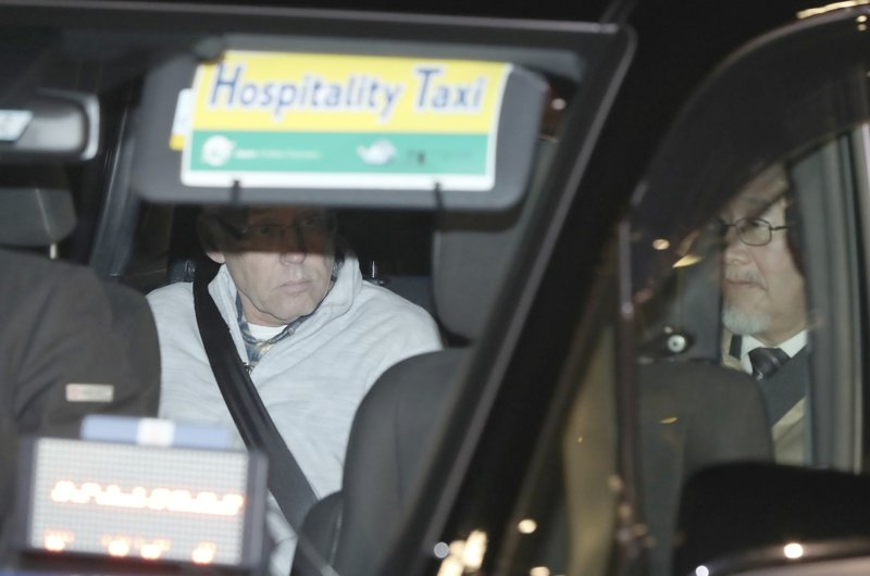In this Tuesday, Dec. 25, 2018, file photo, a car carrying Nissan Motor Co.'s executive Greg Kelly, left, leaves Tokyo's Detention Center in Tokyo. (AP Photo/Eugene Hoshiko, File)