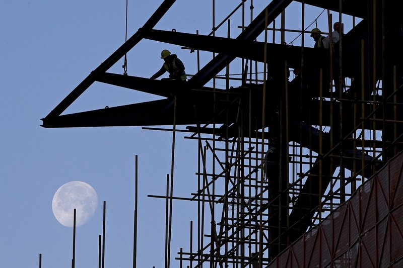In this Tuesday, Dec. 25, 2018, file photo, workers load cables on a steel frames at a shopping mall under renovation, with a backdrop of the moon, in Beijing, Tuesday, Dec. (AP Photo/Andy Wong, File)