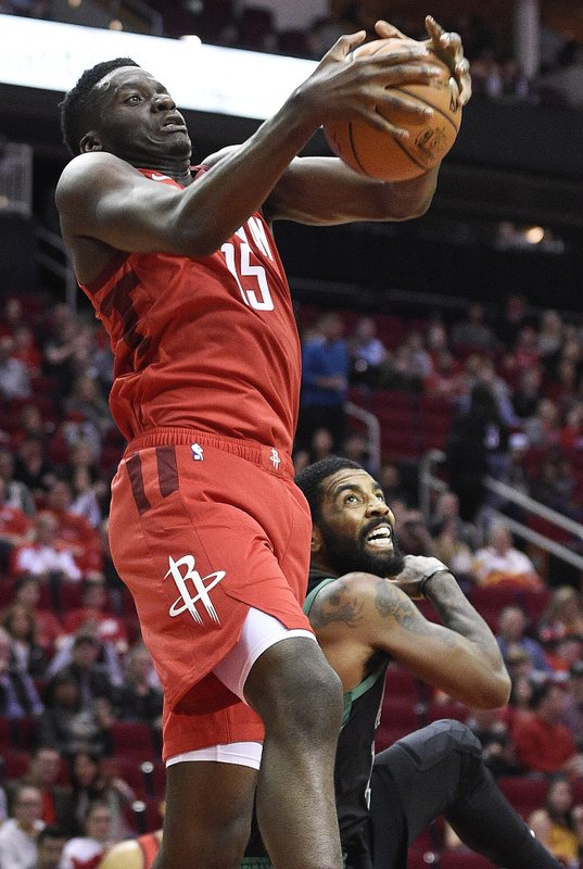 Houston Rockets center Clint Capela, left, grabs a rebound above Boston Celtics guard Kyrie Irving during the first half of an NBA basketball game, Thursday, Dec. (AP Photo/Eric Christian Smith)