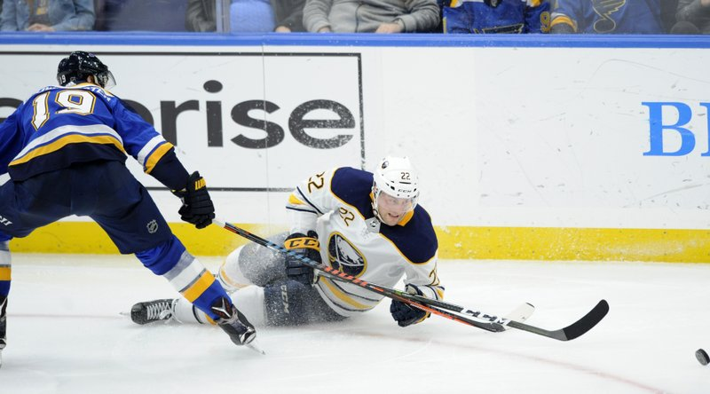 Buffalo Sabres' Johan Larsson (22), of Sweden, reaches for the puck with St. Louis Blues' Jay Bouwmeester (19) during the second period of an NHL hockey game, Thursday, Dec. (AP Photo/Bill Boyce)