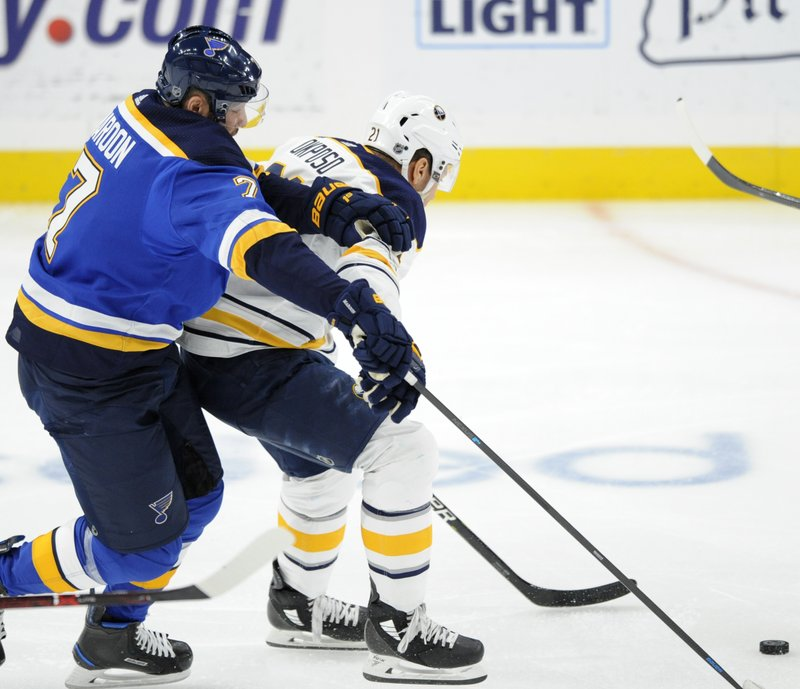 St. Louis Blues' Pat Maroon (7) battles for the puck with Buffalo Sabres' Kyle Okposo (21) during the first period of an NHL hockey game, Thursday, Dec. (AP Photo/Bill Boyce)