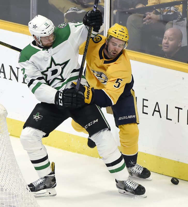 Dallas Stars center Radek Faksa (12), of the Czech Republic, and Nashville Predators defenseman Dan Hamhuis (5) compete for puck during the second period of an NHL hockey game Thursday, Dec. (AP Photo/Mark Zaleski)
