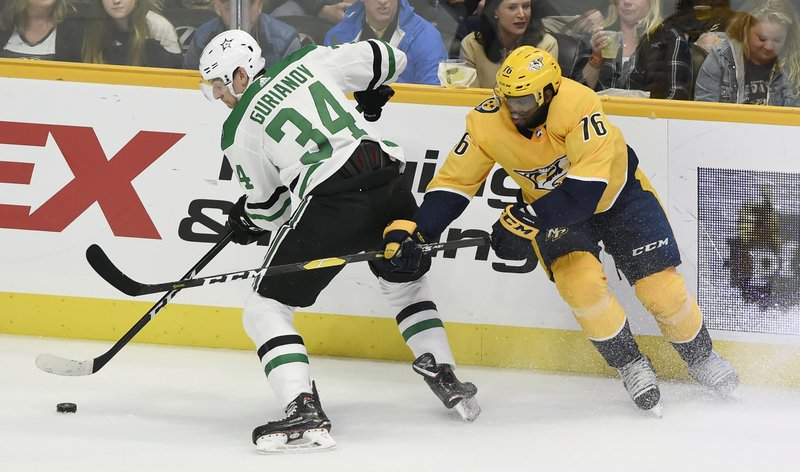 Dallas Stars right wing Denis Gurianov (34), of Russia, moves the puck away from Nashville Predators defenseman P. (76) during the first period of an NHL hockey game Thursday, Dec. 27, 2018, in Nashville, Tenn. (AP Photo/Mark Zaleski)